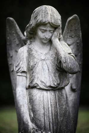 Guardian angel statue forlorn in graveyard