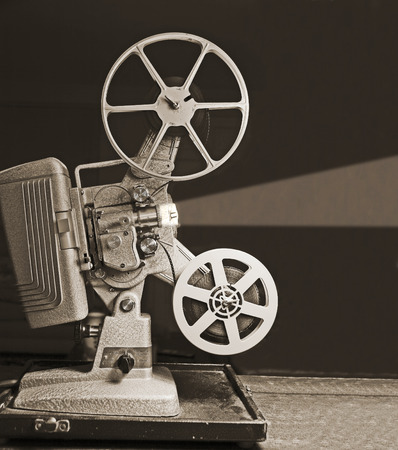 Close-up of the film reels on a vintage 8mm film projector in a dark room