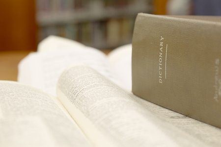thesaurus: Consulting words by using a dictionary. Stock Photo