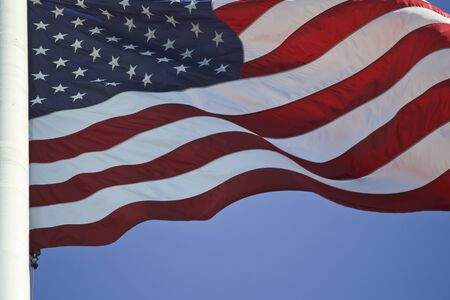 United States flag fluttering under the blue sky Фото со стока