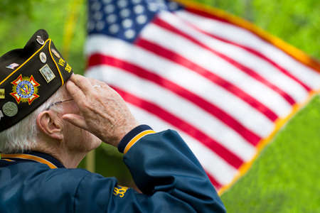 A veteran is saluting in front of US flag.