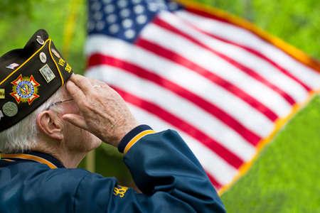 Een veteraan is het groeten in de voorkant van de Amerikaanse vlag.