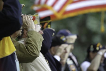 ベテランは、記念日サービスの間に米国旗を敬礼します。