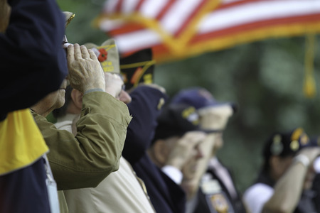 Veteran Salutes the US Flag during  Memorial Day service. Imagens