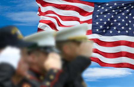 Soldiers and veteran salute in front of the US flag.