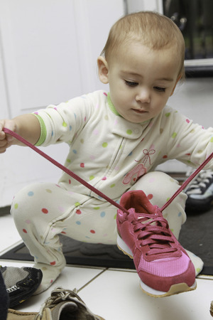 shoelace: One and Half Year baby girl tying shoelace Stock Photo