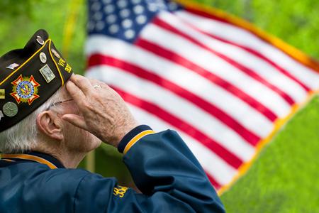 Weteran pozdrawia przed amerykańską flagą.