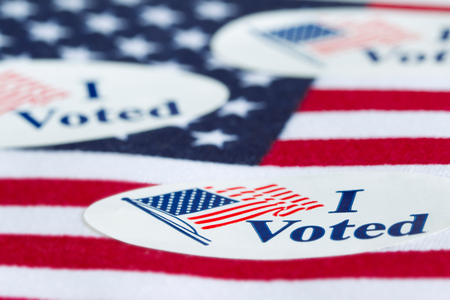 I Voted stickers on the US flag background. Stock Photo