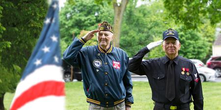 Korean War and Navy veterans saluting at Memorial Day Ceremony Editorial