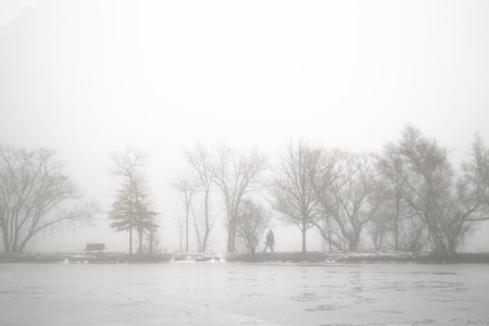 Walking Couple on the bank of lake in the foggy morning