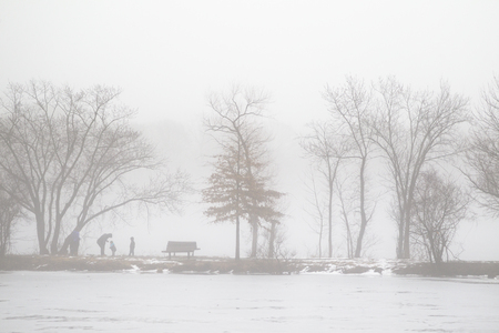 A Family on Lake Bank in Foggy Morning in Winter