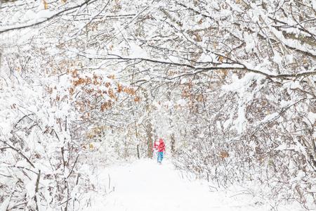 A woman walking in snow woods