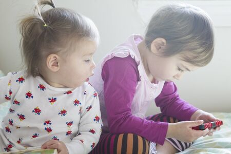 Sisters:4-year-old girl and 1-year-old girl laid in bed watching tablet Stok Fotoğraf - 128440999