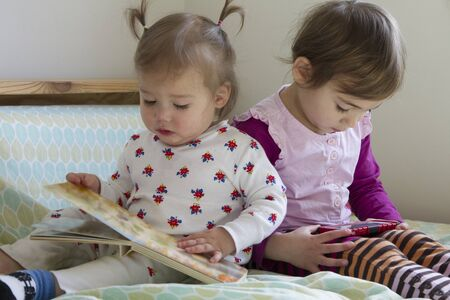 Sisters: 4-year-old girl watching cell phone and 1-year-old girl reading book Stok Fotoğraf