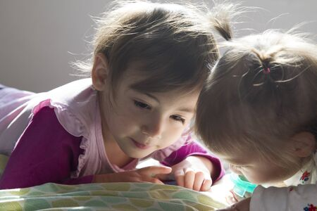 Sisters:4-year-old girl and 1-year-old girl laid in bed watching tablet