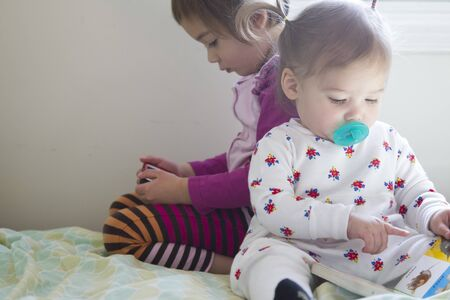 Sisters: 4-year-old girl watching cell phone and 1-year-old girl reading book Stok Fotoğraf - 128441018