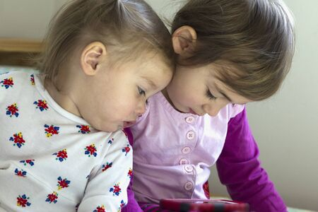 Lovely sisters: 4-year-old girl and 1-old-year girl laid in bed watching tablet Stok Fotoğraf - 128349710