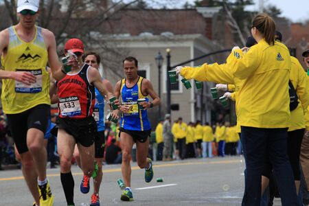 117th Boston Marathon took place in Boston, Massachusetts, on Monday, April 15 (Patriots' Day) 2013. Volunteers offer drink to runners.