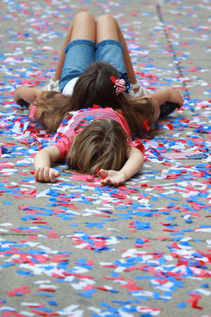 Two girls lay on the ground with confetti