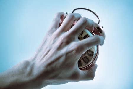 oversleep: Unhappy wake up alarm clock. Hand crushes in a brutal way an alarm clock