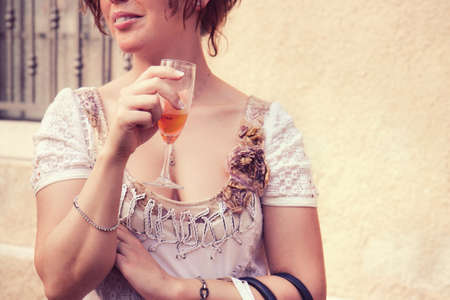 Woman is drinking a cocktail, a young lady is holding a glass outside the bar Stock fotó