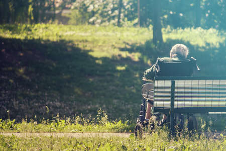 niños abandonados: Grandma sitting on wheelchair, shes abandoned at the park Foto de archivo