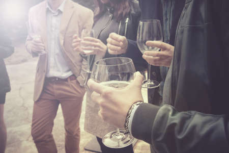 Group of friends drinking wine, people are socializing and having a fun (this version has slightly desaturated colors)