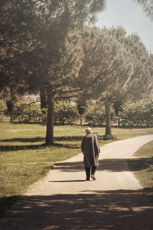 Lonely senior walks alone, elderly abandonment - sadness tone picture Stock Photo