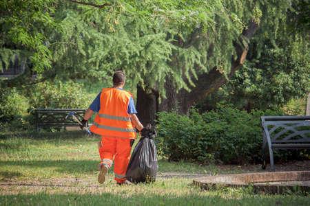 Pracownik sanitarny w parku, człowiek z vis vis. Trzyma worek na śmieci Zdjęcie Seryjne
