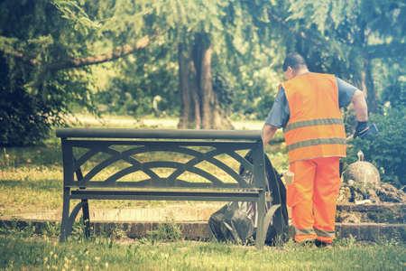 공원에서 일하는 스위퍼, 높은 가시성 조끼를 가진 사람은 벤치 근처에서 쓰레기를 수거합니다. 스톡 콘텐츠