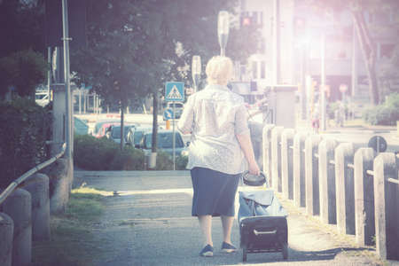 old woman with trolley in the city, female traveler with baggage