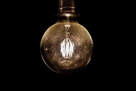 glowing light bulb on black background, dusty vintage object Stock Photo