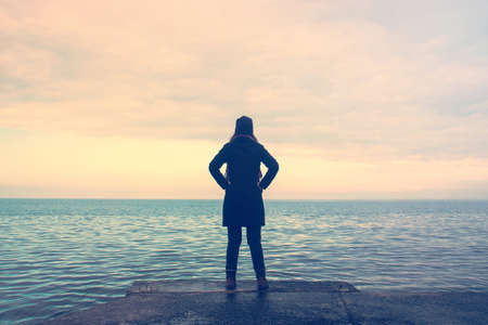 proud woman at the sea, lonely looking at the horizon in winter season