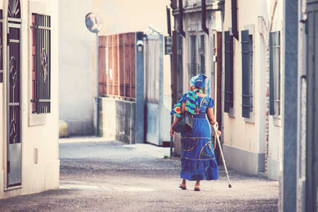 woman with colorful african clothes, female with crutch walking on the street