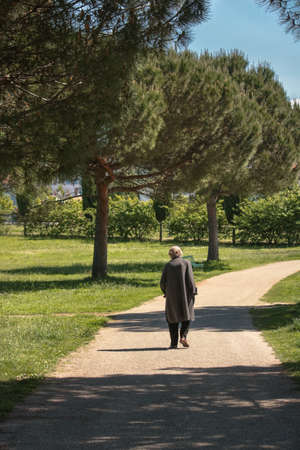 old woman walks alone at the park, elderly abandonment