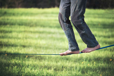 balancing exercise with slackline. Slacklining refers to the act of walking or balancing along a suspended length of flat webbing.