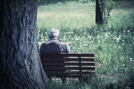 senior is sitting alone on the bench, Elderly gentleman alone on park bench in contemplation (blue tone dramatic effect) Foto de archivo