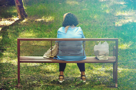 back view of single sad woman, lady sitting alone in a park