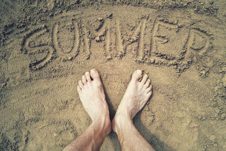 summer word written on the sand. Top view of human feet on summer beach Stock Photo
