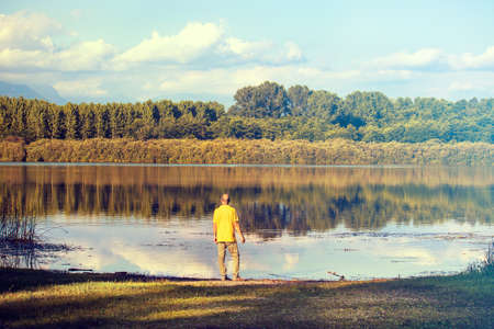 man looking over the lake, middle age person contemplates the quiet of nature Banco de Imagens