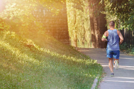 Runner Cardio Workout, sportive man running in a park (copy space available on the left) Stock Photo