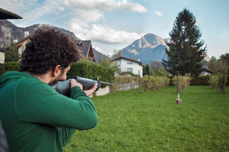 man is doing exercise with a rifle, outdoor sport with green lawn Banque d'images