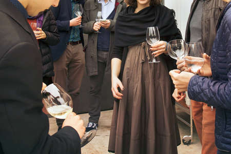 group of boys and girls is drinking wine, people is socializing and having a fun Archivio Fotografico