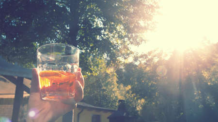 enjoying cocktail in sunset, appetizer to drink outdoor (vintage effect)