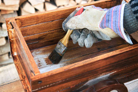 Varnishing a wooden object. Closeup of brush, the hand of worker wears a protection glove