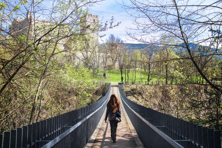 beautiful lady crosses a bridge, on the top of picture there is Brunico's castle in Trentino Alto Adige, Italy Редакционное