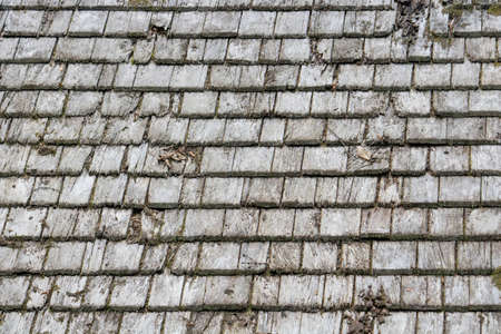damaged wooden roof tiles. Texture of old shingles Фото со стока