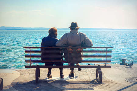 Aged Couple resting on a bench. Woman and man with hat looking the lake