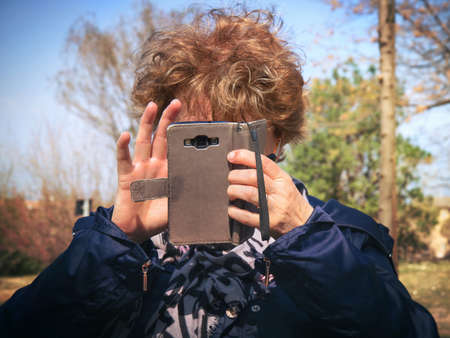middle-aged woman using smartphone, she's at the park and she's tapping on the phone in front of her face