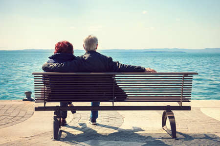 Old couple of lovers on a bench. Back view of romantic seniors dating in front of the lake Фото со стока